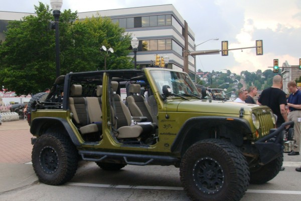 Green Jeep Wrangler Unlimited with doors removed