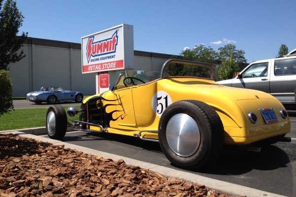 yellow hotrod with cobra in back