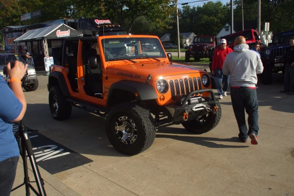 Orange Jeep Wrangler Sport Unlimited with winch and doors removed