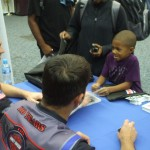 Andrew Hines and Eddie Krawiec share a laugh with a young fan at NSA Bahrain.