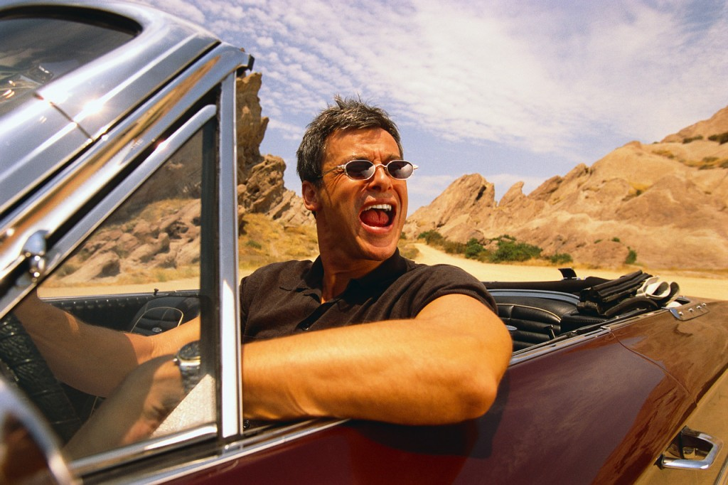 A man drives a maroon convertible in the desert.