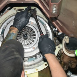 The pressure plate is installed next. Note the alignment tool that inserts through the splines of the clutch disc and engages in the end of the crankshaft. The centers the disc in the clutch assembly, preventing misalignment as the pressure plate is being bolted to the flywheel.
