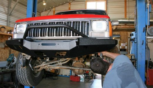 If you don't have a hoist, you'll need at least two people—and probably a third—to position the front bumper and bolt it into place.