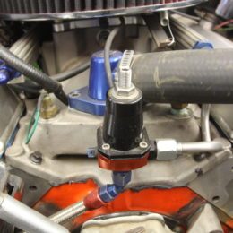 This is an older Aeromotive fuel pressure regulator at the front of a small-block Chevy with a multi-point EFI manifold. The fuel enters the fuel rail on the far left and is regulated after exiting the fuel rail (right). Fuel returns by exiting the regulator at the bottom. (Image/Aeromotive)