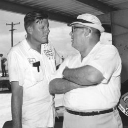 NASCAR Cup car owners Bud Moore, left, and John Holman of the Ford factory Holman-Moody team talk in the garage area during a 1968 NASCAR event. (Image/NASCAR)