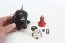 The disassembled fuel pressure regulator illustrates its simplicity. The spring can be adjusted externally with a screw and lock nut. Note the small nipple connection on the dome on both the small red version and the larger black Aeromotive regulator. (Image/Jeff Smith)