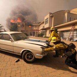Firefighters push a vehicle from a garage as a wildfire fire burns a home near Malibu Lake in Malibu, Calif., Friday, Nov. 9, 2018. (AP Photo/Ringo H.W. Chiu)